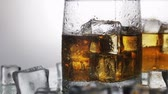 бурбон : whiskey in a glass with ice on a light background in the contour light. Alcoholic beverages. video rotation
