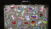 suitcase stickers of the flags of the countries from travels around the world. Rotation video Filmati Stock