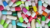 assortment of pharmaceutical medicine capsules, pills and tablets. Rotation video