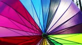 védelme : multi-colored umbrella rotates. umbrella made of different color of fabric strips Stock mozgókép