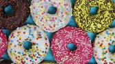 assorted donuts with different fillings and icing on a blue background. top view. Rotation video Filmati Stock