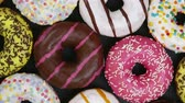 námraza : assorted donuts with different fillings and icing on a black background. top view. Rotation video