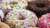 assorted donuts with different fillings and icing. Rotation video Vídeos