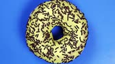 donut with different fillings and icing on blue background. Rotation video. Top view