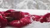 red Cup with a hot drink stands on a stump in the winter forest