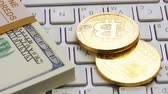 recession : Golden bitcoins and dollar lie on the white keyboard