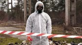 başlık : Man in bio-hazard suit and gas masks stands behind the stripe on the territory full of waste