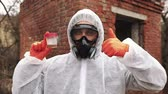 Man in bio-hazard suit and gas mask shows polluted water and non-verbal signs