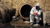 mostaza : Man in bio-hazard suit and gas mask checks the pollution of the water outside