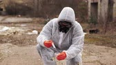 hazardous waste : Man in bio-hazard suit and gas masks takes water and ground for the analysis
