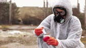 mostaza : Man in bio-hazard suit and gas masks takes water and ground for the analysis
