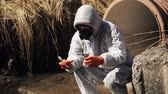 ядерный : Man in bio-hazard suit and gas mask checks the pollution of the water outside