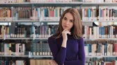 портфель : Thoughtful young woman stands before the shelves in the library Стоковые видеозаписи