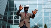 questões : African American man plays in VR headset standing outside
