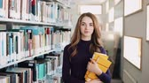 журнал : UKRAINE, LVIV - MARCH 26, 2018: Girl with long hair walks along the shelves in the library. Concept: educational, library, studious and portrait