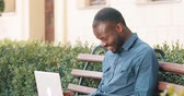 ставить : Attractive African American man working on laptop computer sits on the bench. Received good news excited and happy. Remote freelance work. Success concept Стоковые видеозаписи