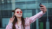 portföy : Pretty young model in red sunglasses takes a selfie on her smartphone. A beautiful girl stands next to the shopping center. Summer time