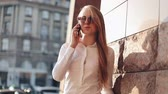 determinado : Young business woman standing near office building at the sunny city streets and talking on a mobile cell phone. Attractive happy girl with sunglasses using cellphone outdoors, sunset