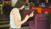 satisfy : Young woman playing games indoor at shopping center, using smart phone. Girl play the popular smartphone game in hypermarket mall Stock Footage