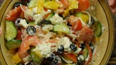 preparations : Stirring fresh vegetable salad with cheese feta in the kitchen . The mixing of vegetables. Close-up