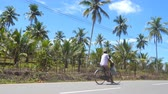 sunny side up : Indian dad and son riding a bicycle along asphalt road in tropical country on sunny day. Asian family cycling on track at countryside. Beautiful scenic of palm trees at background. Side view Close up