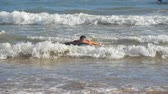 sportos : Young athletic guy paddling out at ocean wave and learning to surfing during summer trip on sunny day. Concept of vacation or holiday. Close up