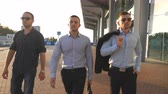 ceo : Portrait of three young businessmen walking in city near office. Business men commuting to work together. Confident guys being on his way to job. Colleagues going outdoor. Slow motion Close up Stock Footage