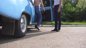 与える : Man opens and holds the door of old car for the beautiful young woman in high heels shoes. Guy opening door of vintage automobile for female passenger. Girl getting into retro auto. Slow Motion