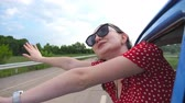 free country : Happy girl in sunglasses leaning out of vintage car window and enjoying trip. Young woman looking out window of moving old retro auto and raising hand. Travel and freedom concept. Slow motion Close up Stock Footage
