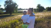 точка зрения : Young dad holding his child on hands at the meadow. Father and son pointing to sun at the field. Happy family spending time together. Summer landscape at background. Closeup Rear back view Slow motion