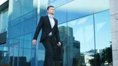 stadt straße : Young businessman with a briefcase walking in city street near modern office building. Confident guy in suit being on his way to job. Portrait of business man commuting to work. Slow motion Close up Stock Footage