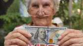 Франклин : Old woman in eyeglasses showing one hundred dollar bill into camera outdoor. Happy grandmother holding foreign currency outside. Money concept. Close up Slow motion