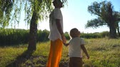 Little child looking up on a tall tree during walking with dad through green park at summer day. Young father and cute son spending time together outdoor. Sunlight at background. Slow motion Close up 動画素材