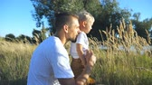 Profile of young dad sitting with his cute son with blonde hair at grass on a sunny summer day. Happy family spending time together at nature. Beautiful nature at background. Slow motion Close up