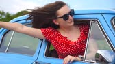 Young girl in sunglasses leaning out of vintage car window and enjoying trip. Woman looks out from moving retro auto. Travel concept. Blurred background. Slow motion Close up