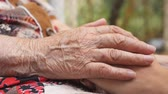 senior people : Hand of old women stroking young female arms outdoor. Granddaughter and grandmother spending time together outside. Concept of care and love. Close up Side view Slow motion Stock Footage