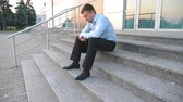 depresja : Close up of upset sad manager sitting on stairs near office building and crying. Desperate young businessman got a very bad news on phone and feeling despair outdoor. Concept of financial crisis