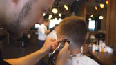 aparando : Professional hairstylist cutting hair of guy with electric razor in barbershop. Hairdresser making male haircut to customer with clipper in salon. Head of client is blurred. Close up Slow motion