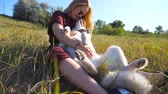 hond : Young girl with blonde hair sitting on grass at field and caress her siberian husky. Beautiful woman in sunglasses smiling and kissing her pet at meadow. Happy dog licking female face. Close up