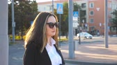empleador : Profile of young businesswoman walking along urban street at sunset time. Business woman going to work. Confident girl being on his way to office. Sun flare at background. Slow motion Close up Archivo de Video