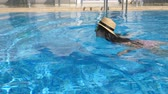 pływak : Young beautiful girl in sunglasses and hat swimming in pool. Woman relaxing in clear warm water on sunny day. Summer vacation or holiday concept. Close up Slow motion Wideo