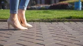 stopy : Female legs in high heels shoes walking in urban street. Feet of young woman in high-heeled footwear going in city. Girl stepping on sidewalk. Low angel view Slow motion Close up