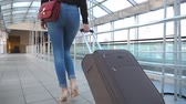 ロビー : Legs of business woman going through hall of terminal with her luggage. Unrecognizable girl in high heels stepping and roll suitcase on wheels. Lady goes on trip. Travel concept. Slow motion Close up 動画素材