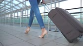 stopy : Legs of business woman going through hall of terminal with her luggage. Girl in high heels stepping and roll suitcase on wheels. Concept of work trip or travel. Slow motion Close up