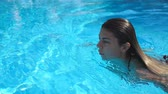 plavec : Profile of young woman refreshing and swimming in pool of hotel with blue clear water. Beautiful girl floating at basin and relaxing during vacation. Lady enjoying resting on resort. Slow motion Dostupné videozáznamy