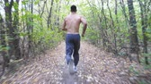 motivatie : Unrecognizable muscular sportsman running along trail at early autumn forest. Young athlete sprinting along path at nature. Guy training outdoor. Concept of healthy active lifestyle. Rear view Stockvideo