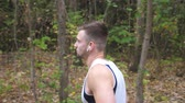 coureur : Young sporty man running along trail near forest at early autumn. Handsome sportsman with wireless headphones jogging outdoor. Athletic guy exercising at nature. Healthy active lifestyle. Side view