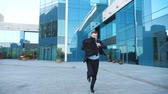 evrak çantası : Young businessman with briefcase runs and looks at his watch. Confident guy late for meeting. Successful man in suit jogging near modern building. Handsome man in hurry to appointment. Slow motion Stok Video