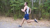 coureur : Handsome strong sportsman with wireless headphones sprinting fast along trail near forest. Sporty man running along road at nature. Athletic guy exercising at early autumn. Healthy active lifestyle
