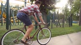 flare light : Young handsome man riding a vintage bicycle at amusement park. Sporty guy cycling outdoor. Sun shine at background. Healthy active lifestyle. Close up Slow motion